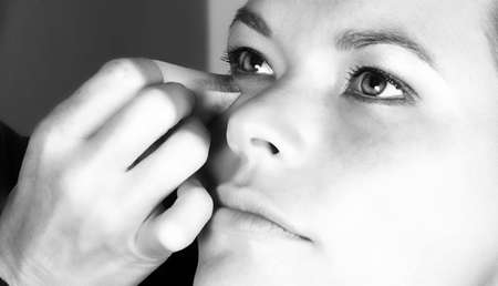womanhood:  Make-up artist applying foundation to young woman�s face 0 black and white