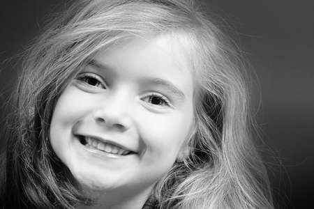 Cute blond girl with strong eye-contact and big smile Stock Photo - 438697