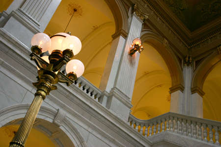sconce: Brass lamppost illuminates grand arches and columns