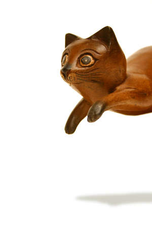 Wooden cat statue caught in a playful pounce. Clipping path included.