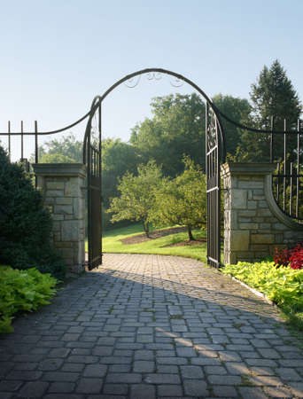 iron gate: Light beckons through a stone and iron gateway. Stock Photo