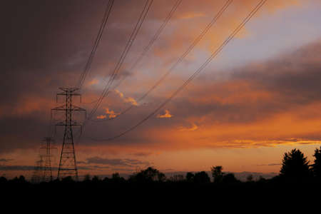 Silhouettes of power lines and towers with a brilliant sunset Imagens
