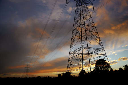 Silhouettes of power lines and towers with a brilliant sunset Stock Photo