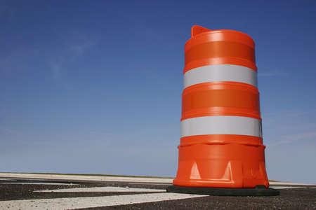 roadwork: One orange construction barrel signaling roadwork ahead.