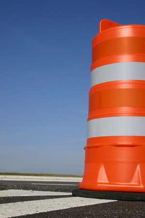 One orange construction barrel signaling roadwork ahead.