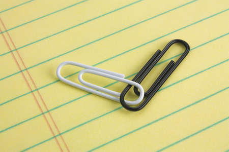 Black and white paper clips connected on a legal pad of paper Stock Photo - 4105050