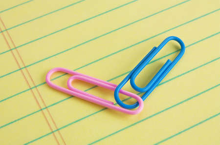 legal pad: Pink (female) and blue (male) paper clips connected on a legal pad of paper Stock Photo