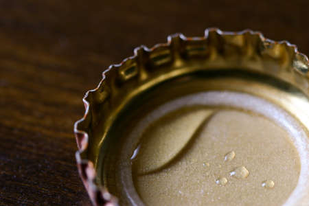 Macro closeup on a beer bottle cap on a bar