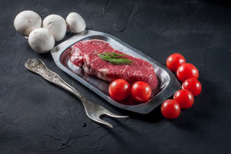 new york strip: Raw steak with tomatoes, mushrooms and dill.