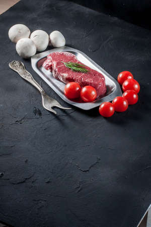 Raw steak with tomatoes, mushrooms and dill. photo