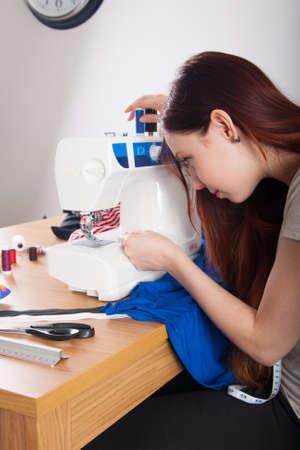 plain stitch: Woman passing thread through the eye of a needle