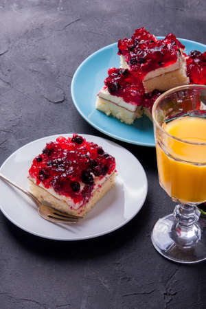 Piece of forest fruit cake with jelly and cream on a plate with orange juice. Stack of cake in the background