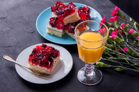 fruit plate: Piece of forest fruit cake with jelly and cream on a plate with orange juice. Stack of cake in the background