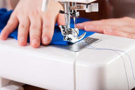 plain stitch: Young woman sewing fabric on sewing machine