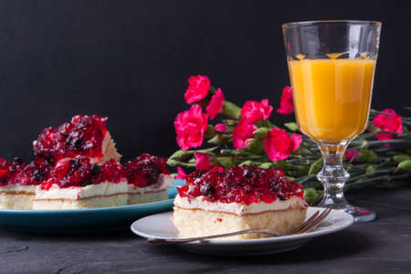 gillyflower: Piece of forest fruit cake with jelly and cream on a plate with orange juice. Stack of cake in the background
