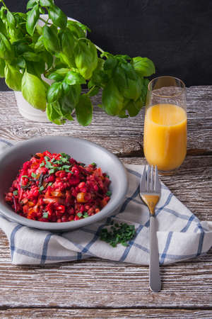Bowl of buckwheat groats with vegetables and glass of orange juice on wooden table