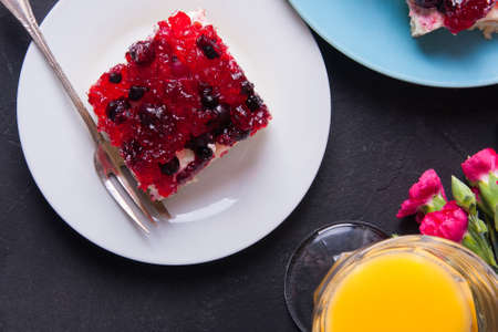 gillyflower: Piece of forest fruit cake with jelly and cream on a plate with orange juice. Stack of cake on a plate