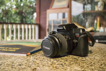 Old school Canon EOS 888 with notebook and pecil on a table