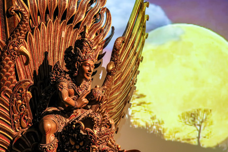 Wooden sculture of Vishnu mounted on Garuda with full moonlight Stock Photo