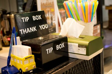 A tip box, tissues box and drinking straws on a coffee shop's counter Stock fotó