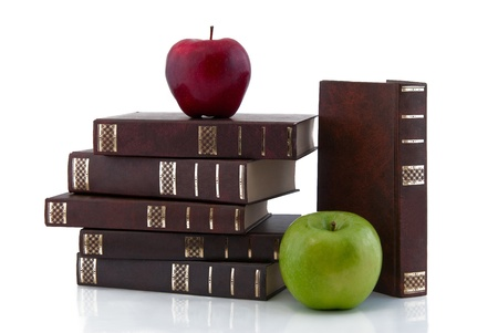 Books combined by a pile and apples, isolated on white background