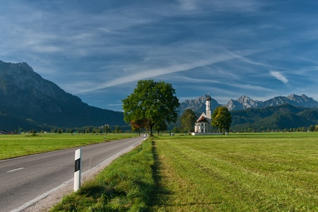 Autumn landscape with road, tree, church, mountains and sky on background Stock Photo - 12434855
