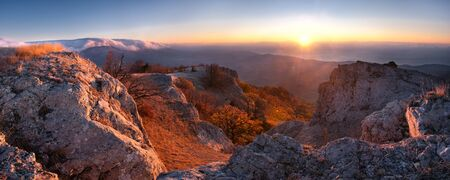 Sunrise panorama in the mountain, first sun rays through clouds photo