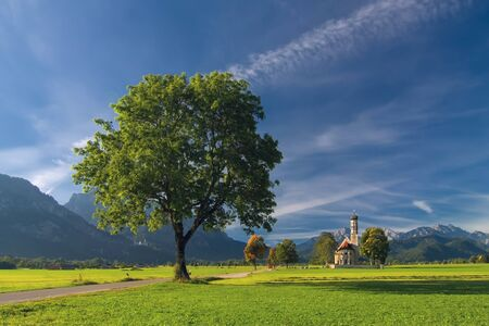 Autumn landscape with road, tree, church, mountains and sky on backgruond photo