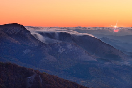 Sunrise in the mountain, first sun rays through clouds Stock Photo - 12961304