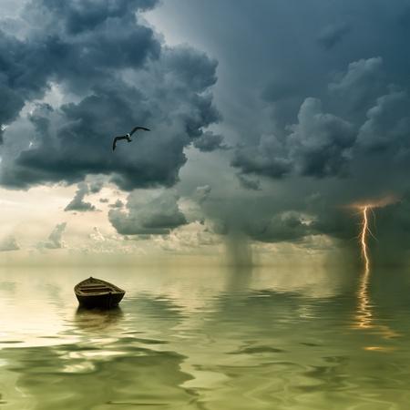 bateau: Le vieux bateau solitaire � l'oc�an, se rapproche d'un orage avec de la pluie et de la foudre sur fond Banque d'images