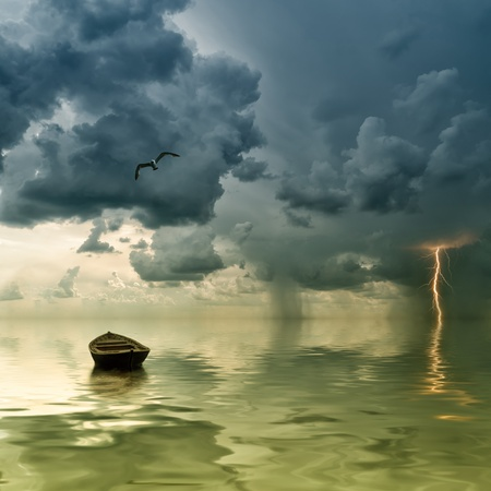 yellow boats: The lonely old boat at the ocean, comes nearer a thunder-storm with rain and lightning on background Stock Photo