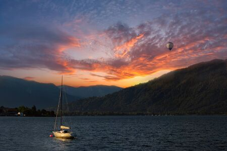 Colorful sunset on Lake, with yacht on water and air baloon in the sky, Alpes mountains on background photo