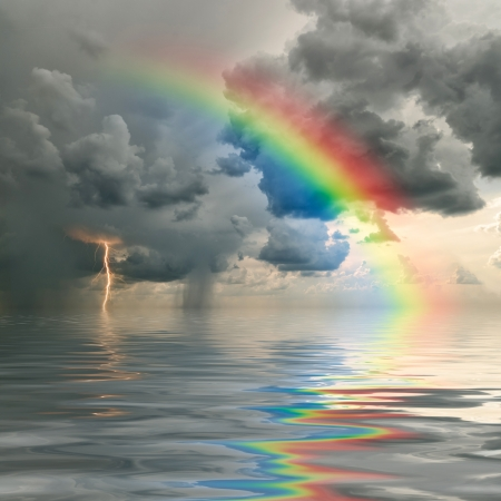 rainbow scene: Colorful rainbow over ocean, thunderstorm with rain and lightning on background Stock Photo