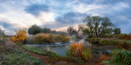 Beautiful autumn landscape on morning river with fog, majestic clouds in the sky. Panorama