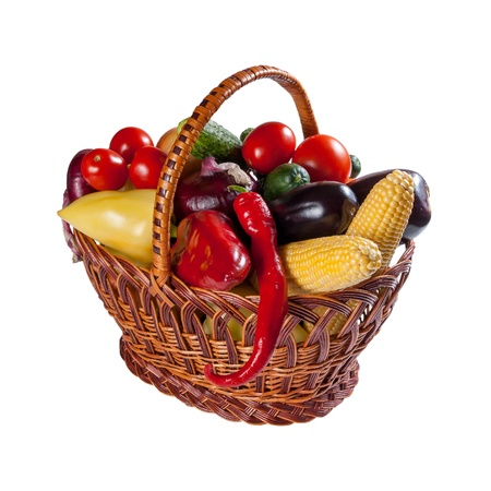 Different fresh vegetables in wicker basket isolated on a white background photo