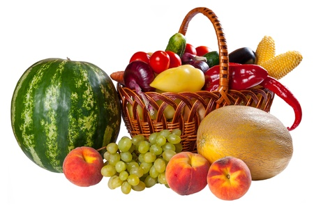 Different fresh vegetables in wicker basket and fruit isolated on a white background photo