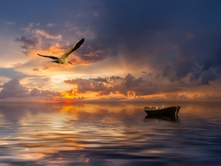 Beautiful landscape with lonely boat and birds against a sunset, majestic clouds in the sky Stockfoto