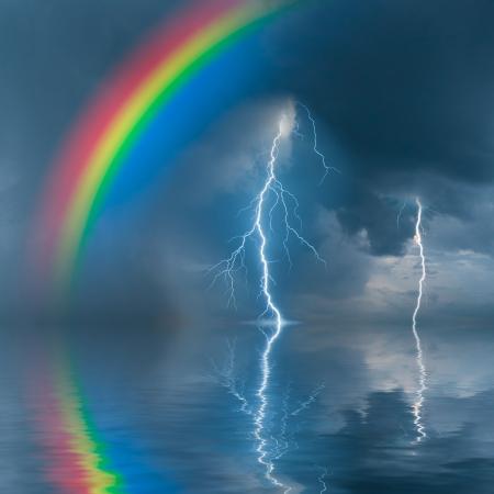 Kleurrijke regenboog boven water, onweer met regen en bliksem op de achtergrond Stockfoto