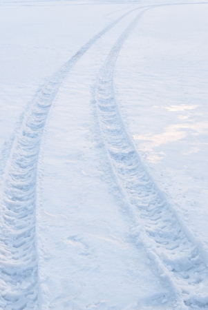 Tire trace on snow leaving to the horizon photo
