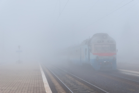Commuter train on railway station in fog Stock Photo - 15804704