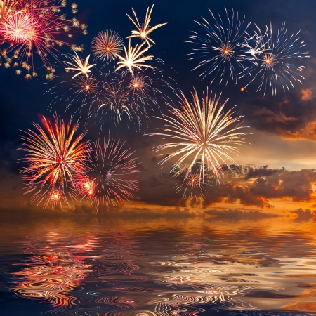 july: Beautiful colorful holiday fireworks in the evening sky with reflection and majestic clouds, long exposure