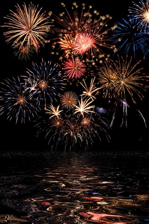 Beautiful colorful holiday fireworks with reflection on the black sky background,  long exposure