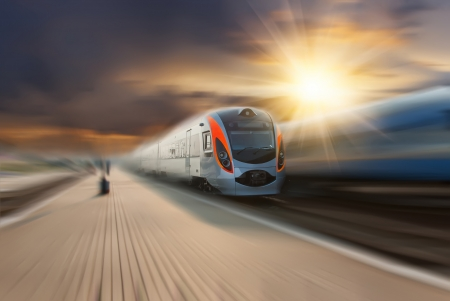 High-speed train passing station with motion blur, majestic clouds and sun on background photo
