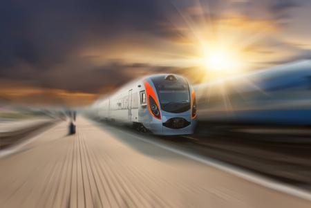 estacion tren: Tren de alta velocidad pasando la estaci�n con el desenfoque de movimiento, las nubes y el sol majestuosas en el fondo