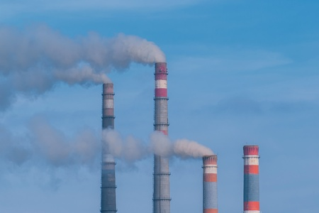 Close-up tops of smoking pipes of power plant on blue sky background photo