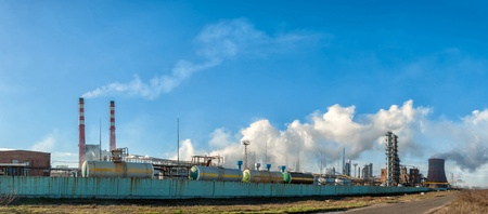 Panorama of the chemical factory throwing out polluting smoke from pipes in the blue sky photo