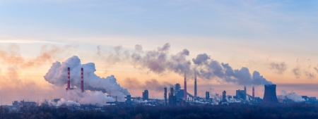Panorama of the chemical factory throwing out polluting smoke from pipes in the morning sky