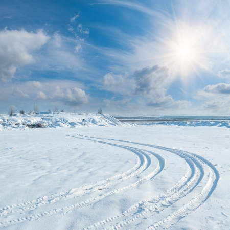 Winter landscape with tire trace on snow leaving to the horizon, sun and clouds in sky