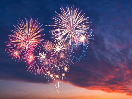 Beautiful colorful holiday fireworks in the evening sky with majestic clouds,  long exposure photo