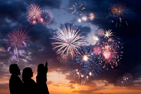 The happy family looks beautiful colorful holiday fireworks in the evening sky with majestic clouds,  long exposure photo